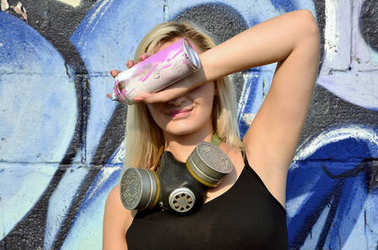 Young and beautiful smiling sexy girl graffiti artist with gas mask on her neck hiding his eyes with a spray can standing on a wall background with a graffiti pattern in blue and purple tones