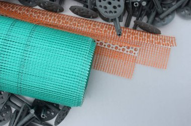 A set of construction items for the insulation of walls. Plastic dowels, a roll of mesh for the insulation of facades and a corner profile with a grid lie on the foam polystyrene surface