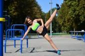 Fotografie Mladý bělošský sportovkyni v zářivě zelené sportovní oblečení cvičit nohy jezdí na sportovní gym pro aktivní rekreaci. Letní sporty a zdravého životního stylu
