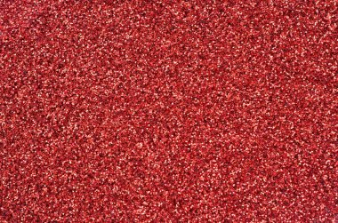 A huge amount of red decorative sequins. Background texture with shiny, small elements that reflect light in a random order. Glitter texture