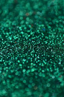 A huge amount of green decorative sequins. Background texture with shiny, small elements that reflect light in a random order. Glitter texture