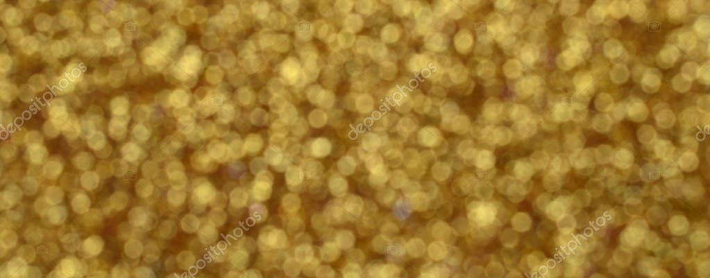 A huge amount of yellow decorative sequins. Blurred background image with shiny bokeh lights from small elements that reflect light in a random order