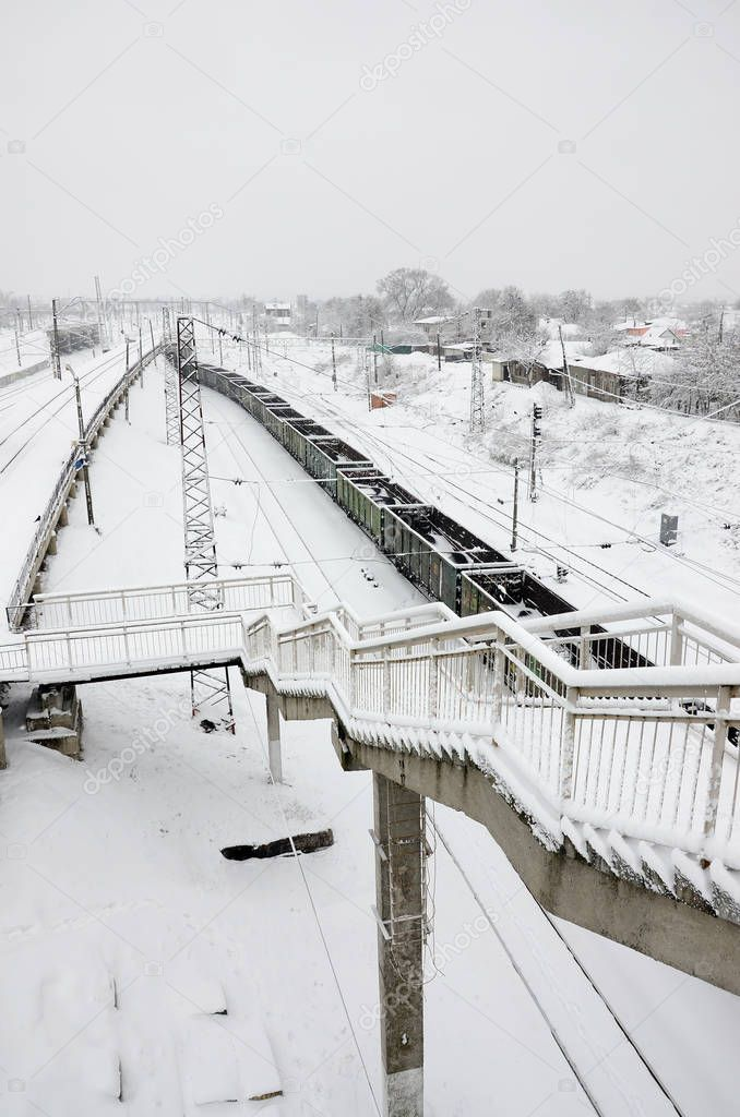 A long train of freight cars is moving along the railroad track. Railway landscape in winter after snowfall