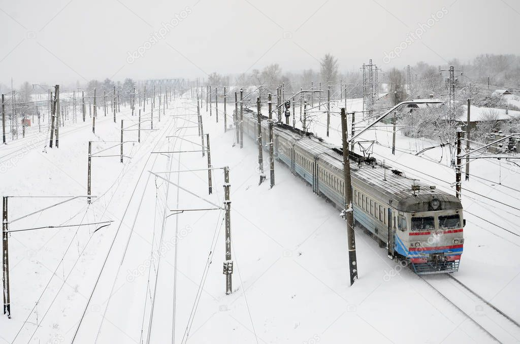 A long train of passenger cars is moving along the railway track. Railway landscape in winter after snowfall