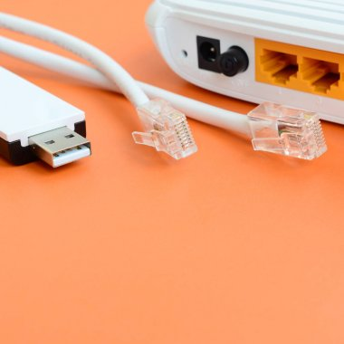 Internet router, portable USB wi-fi adapter and internet cable plugs lie on a bright orange background. Items required for internet connection