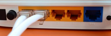 The Internet cable plugs are connected to the Internet router, which lies on a bright orange background. Items required for Internet connection