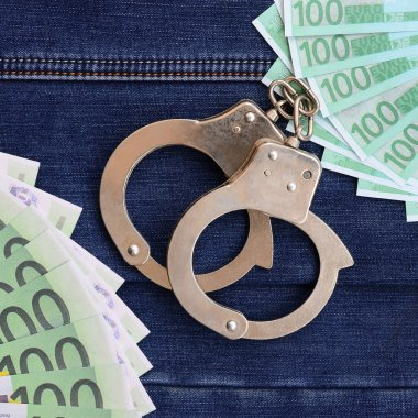 The fan of a lot of euro bills and police handcuffs is on a dark denim surface. Background image