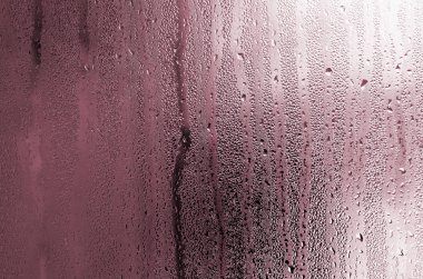 Texture of a drop of rain on a glass wet transparent background. Toned in pink color