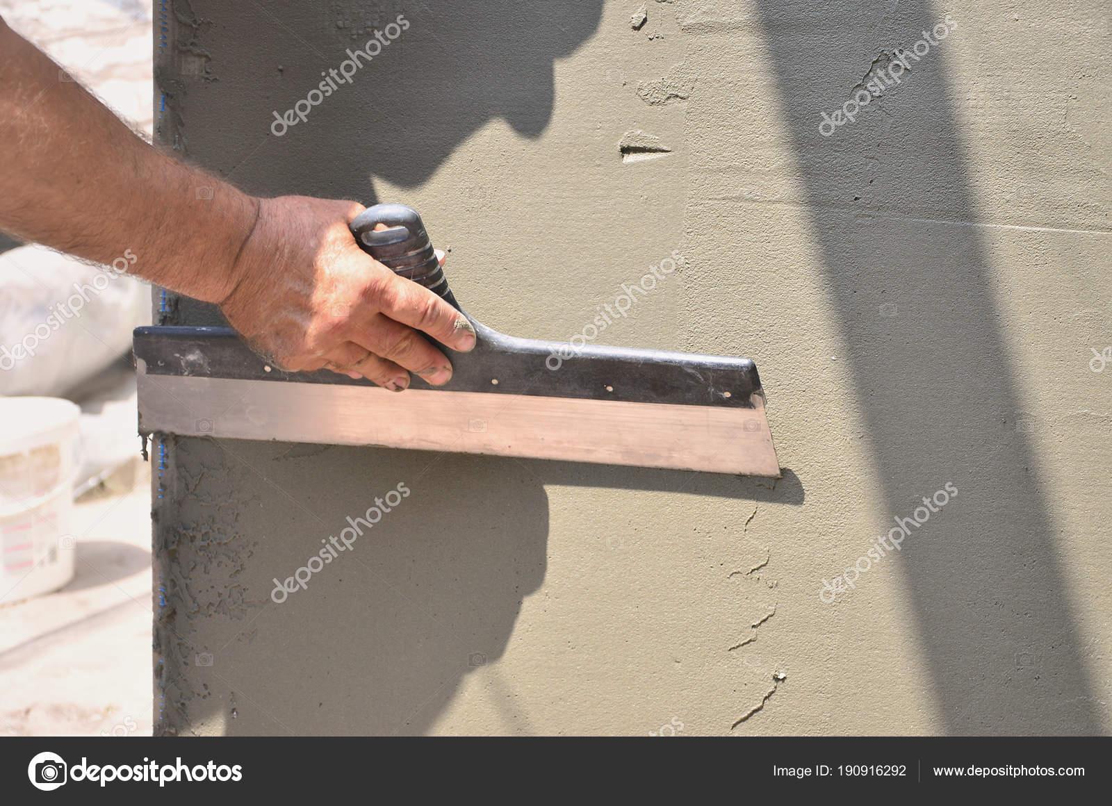 hände eines alten manuellen arbeiter mit wand verputzen werkzeuge