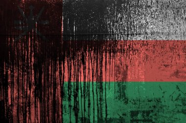 Oman flag depicted in paint colors on old and dirty oil barrel wall close up. Textured banner on rough background