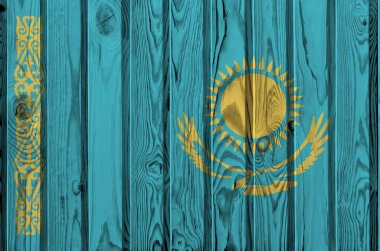 Kazakhstan flag depicted in bright paint colors on old wooden wall close up. Textured banner on rough background