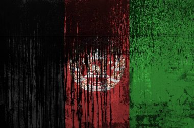 Afghanistan flag depicted in paint colors on old and dirty oil barrel wall close up. Textured banner on rough background