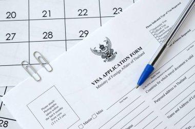 Thailand Visa application form and blue pen on paper calendar page