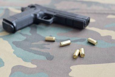 9mm bullets and pistol lie on camouflage green fabric. A set shooting range items or a self-defense kit. Golden shells near handgun stock vector