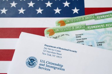 United States Permanent resident green cards from dv-lottery lies on United States flag with envelope from Department of Homeland Security