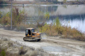 Fotografie Quarry aggregate with heavy duty machinery. Caterpillar loader Excavator with backhoe driving to construction site quarry