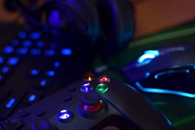 Modern gamepad and gaming mouse lies with keyboard and headphones on table in dark playroom scene. Gameplay streaming and video game walkthroughts concept