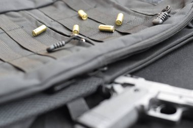 9mm bullets and pistol lie on a black tactical backpack
