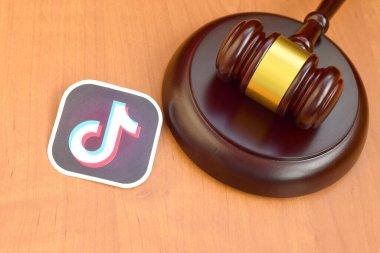 KHARKOV, UKRAINE - FEBRUARY 17, 2020: Tiktok paper logo lies with wooden judge gavel. Entertainment lawsuit concept