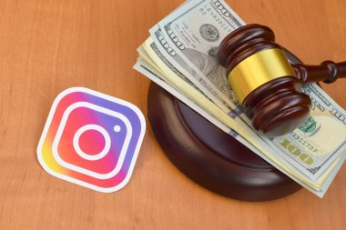 KHARKOV, UKRAINE - FEBRUARY 17, 2020: Instagram paper logo lies with judge gavel and hundred dollar bills. Entertainment lawsuit concept stock vector