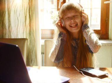 happy young girl at home smiling listening music with head phone