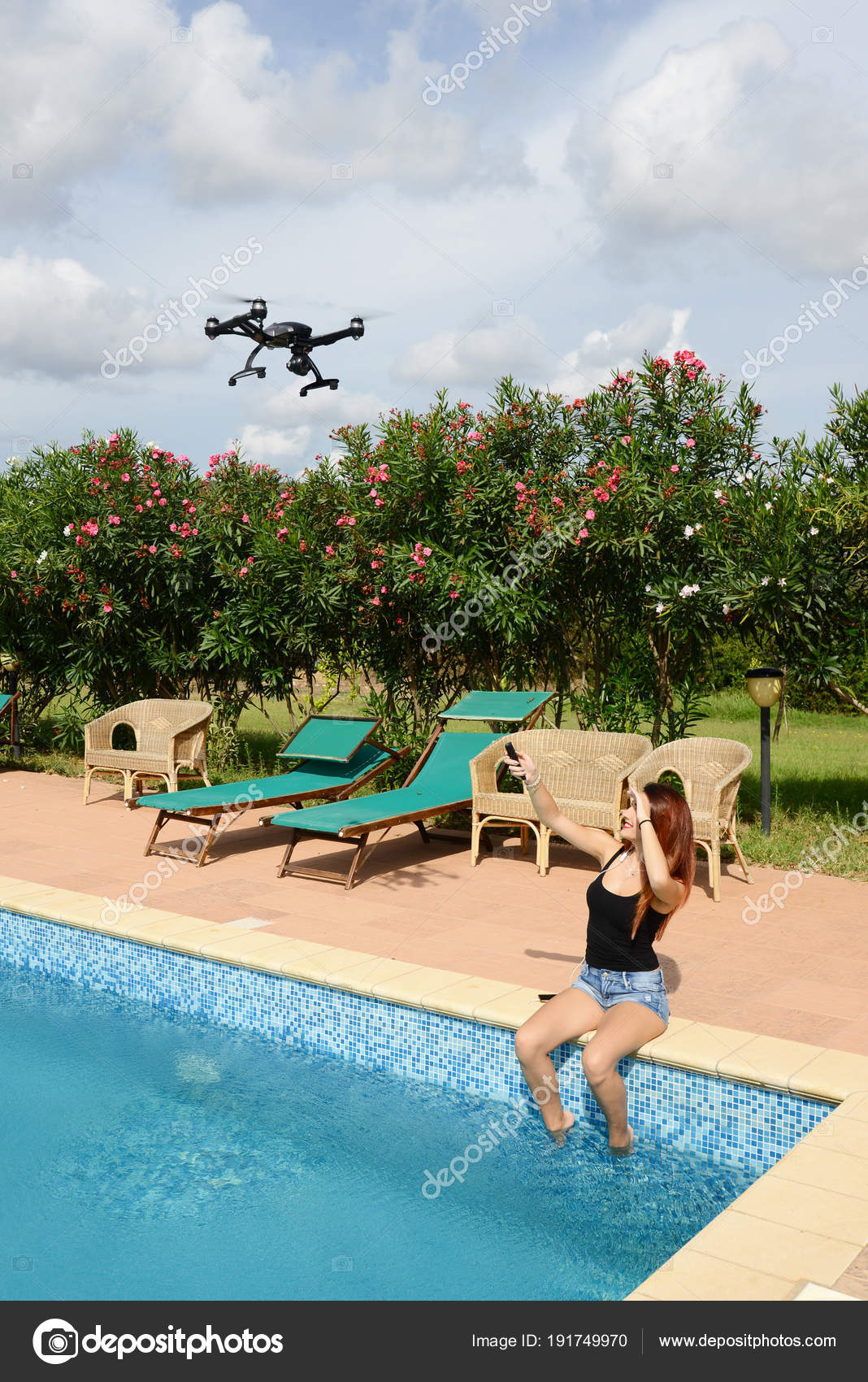 Girl fly drone with remote control by the swimming pool ...