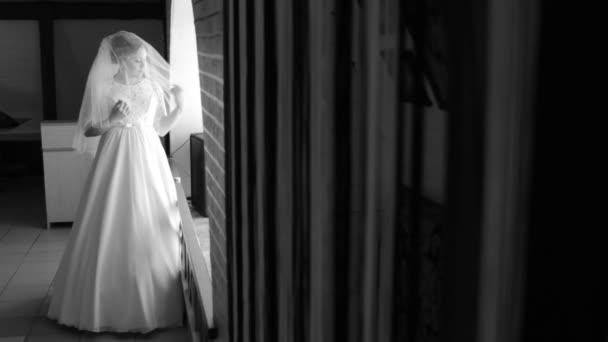 Krásná, něžná nevěsta, stál jsem u okna. Upraví její závoj. Při pohledu z okna. Černobílý obrázek