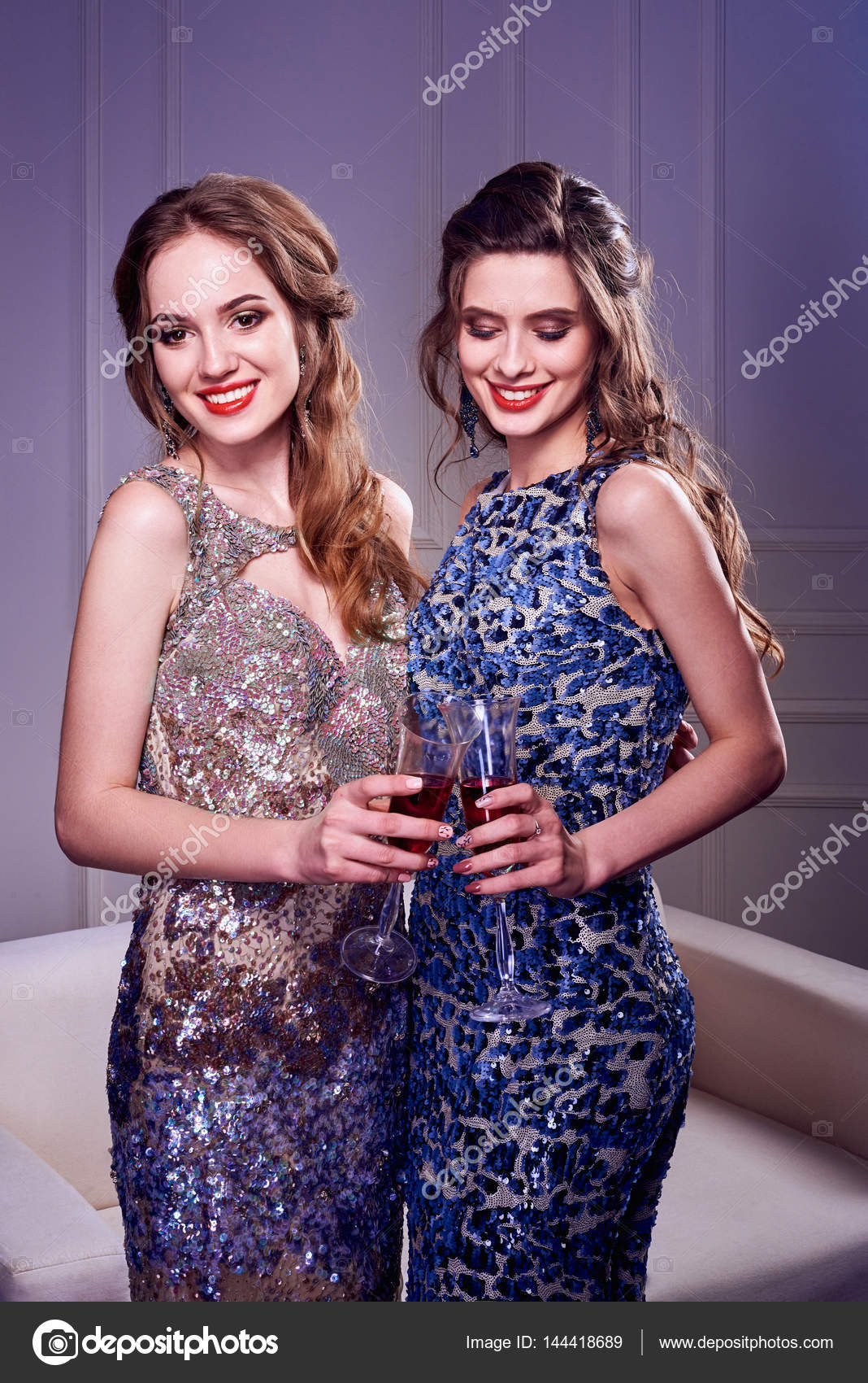 Retrato de dos elegantes mujeres jóvenes con una copas de champagne ...