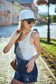 Girl wearing white t-shirt, jeans and baseball cap posing, minimalist urban clothing style, for print store
