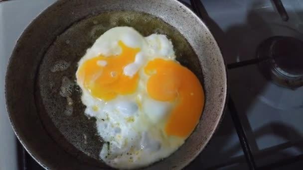 séf évszakok egy sütő tojás, napos oldalon felfelé, őrölt bors egy kis serpenyőben egy ipari gáz égő tűzhely felett