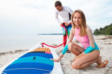 Young couple with sup board on the beach
