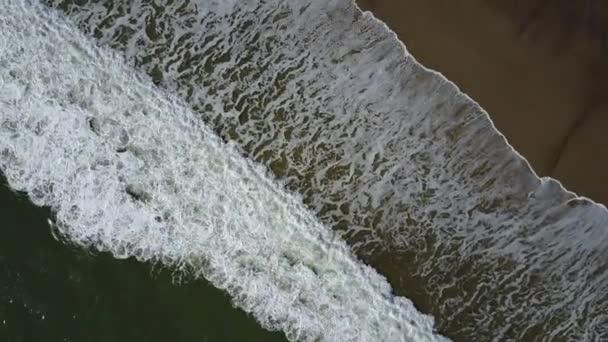 Letecký pohled na vlny oceánu shazovat na pláži s lidmi okolo, 4 k drone záběry
