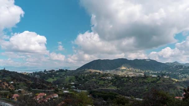 Gyönyörű Timelaps mozi shot 4k. Kilátás a Hollywood Hills a Hollywood-jel. Szép felhők és a hegyek mozoghat. Egy ragyogó napsütéses napon, Hollywood, Los Angeles, California
