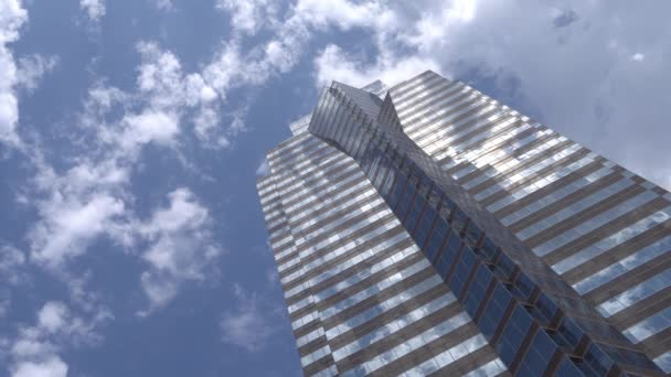 Tall skyscraper on a background of moving clouds. Blue sky with white clouds. Reflection of clouds with glass windows of a skyscraper.
