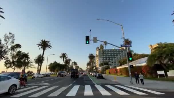 Santa Monica, Kalifornie, USA - 15. prosince 2019: Řízení auta na Santa Monica Ocean Ave při západu slunce. Teplý slunečný den v Santa Monica Los Angeles California Usa.