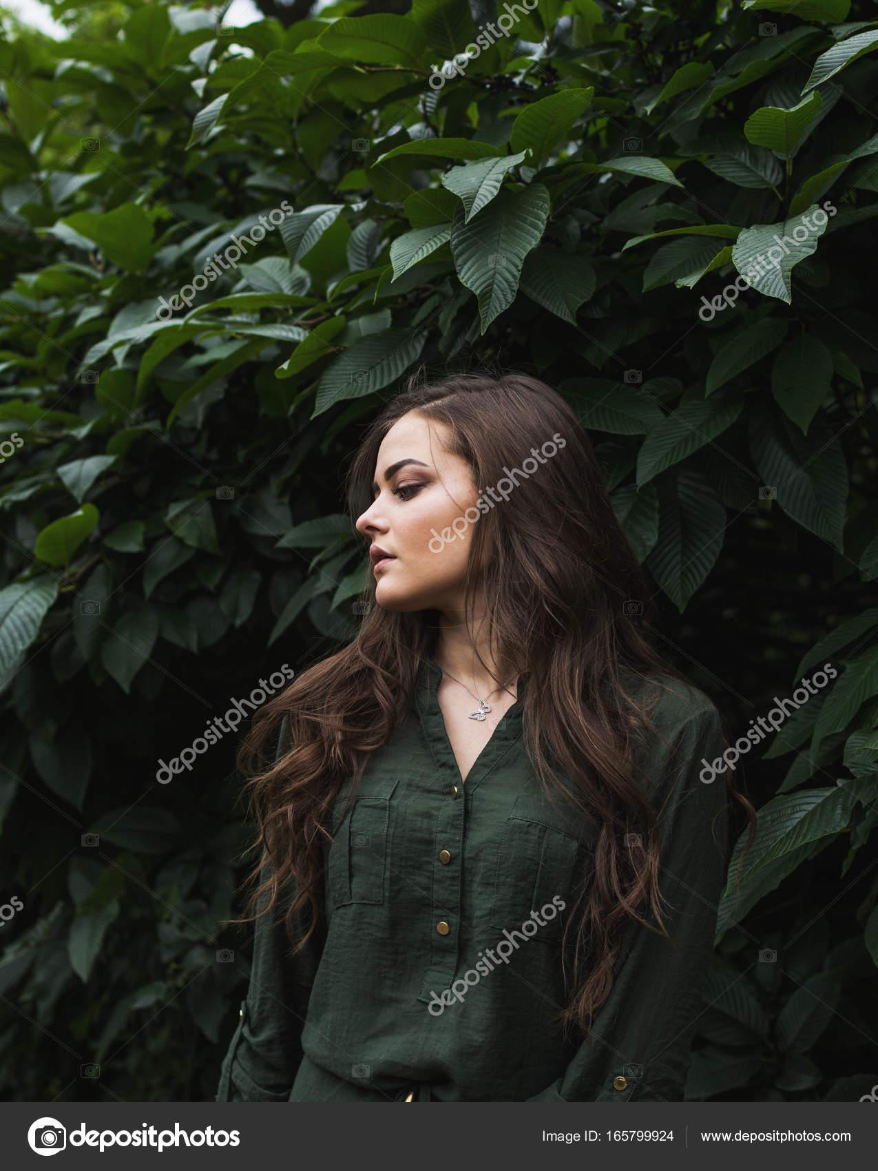 2a29eed54588 Όμορφη εφηβική μοντέλο ντυμένος με μόδας πράσινο φόρεμα θέτοντας σε εξωτερικούς  χώρους σε πάρκο. Τονισμένα με ζεστά χρώματα — Εικόνα από ...