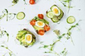Photo Tasty sandwiches with egg, avocado and vegetables on wooden white rustic background. Flat lay