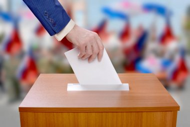 Man votes by throwing a ballot in the ballot box