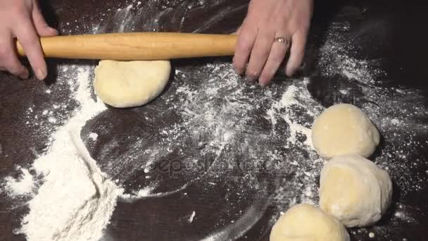 Female hands roll out the dough on the table
