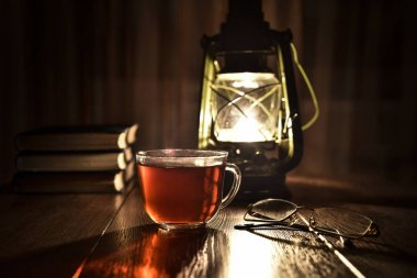 The light of kerosene lamp, cup of tea and books on the table