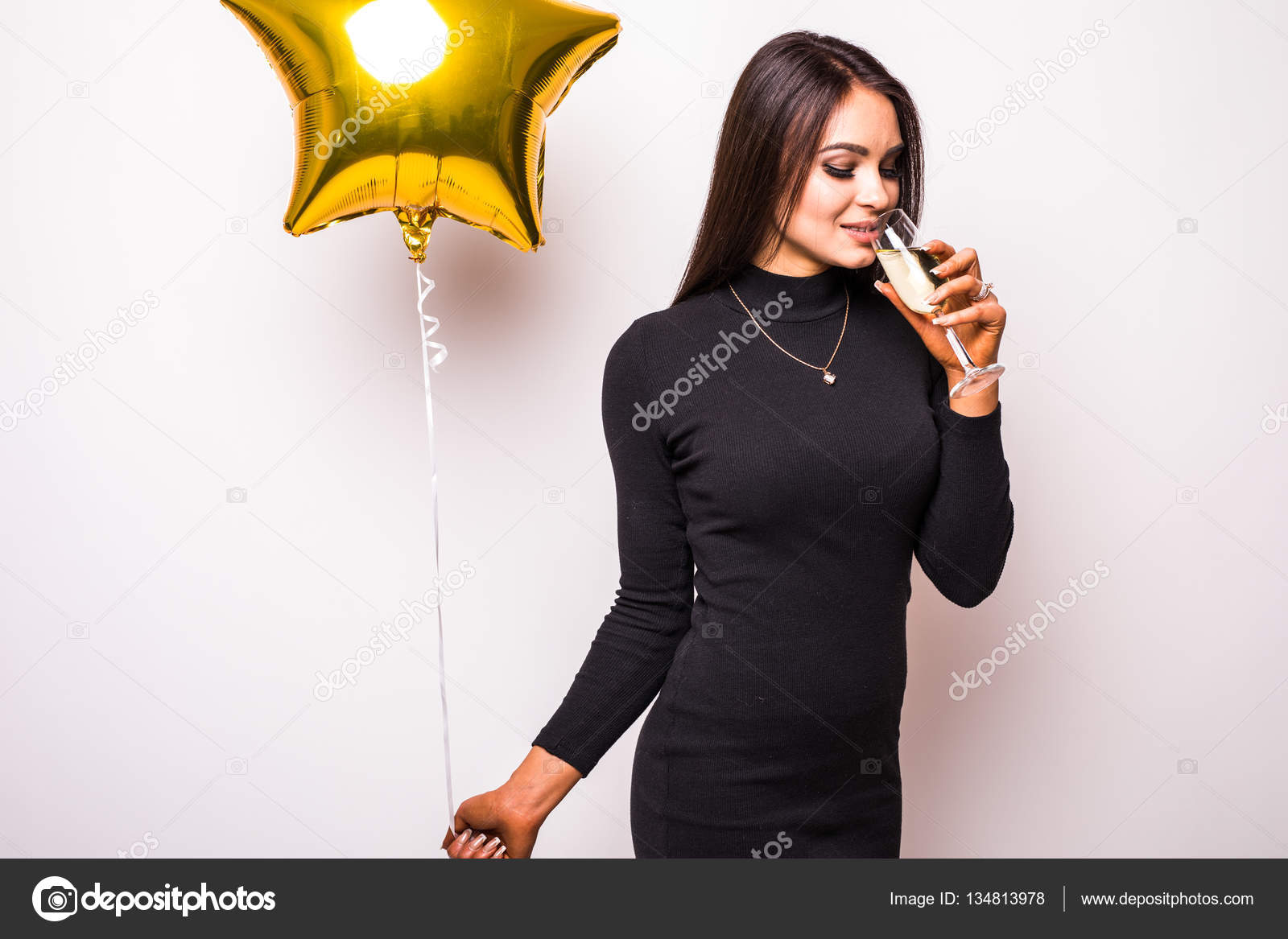 2ecd8a01a416 Pretty young woman in black dress with gold star shaped balloon smiling and drinking  champagne over white background — Photo by dan.grytsku.gmail.com| ...