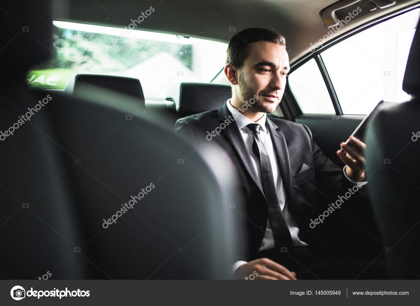 Seguro joven empresario marco su teléfono inteligente y mirando a ...