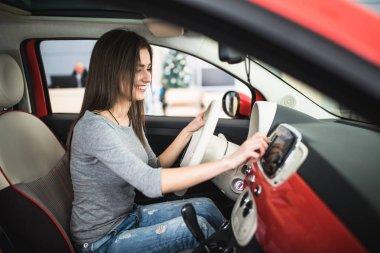 Car dashboard. Radio closeup. Woman sets up button on dashboard