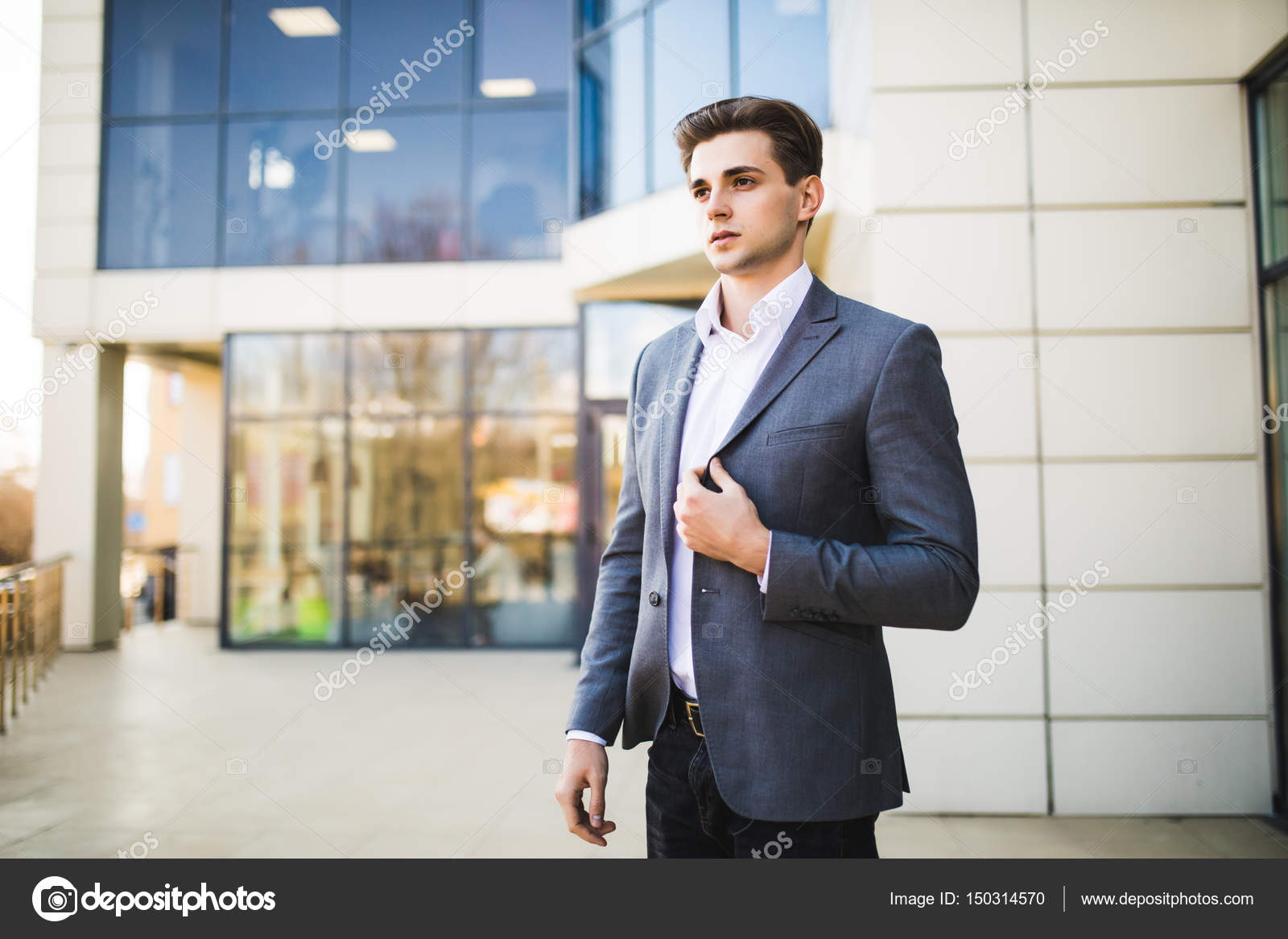 successful business man outdoors in front of office building stock