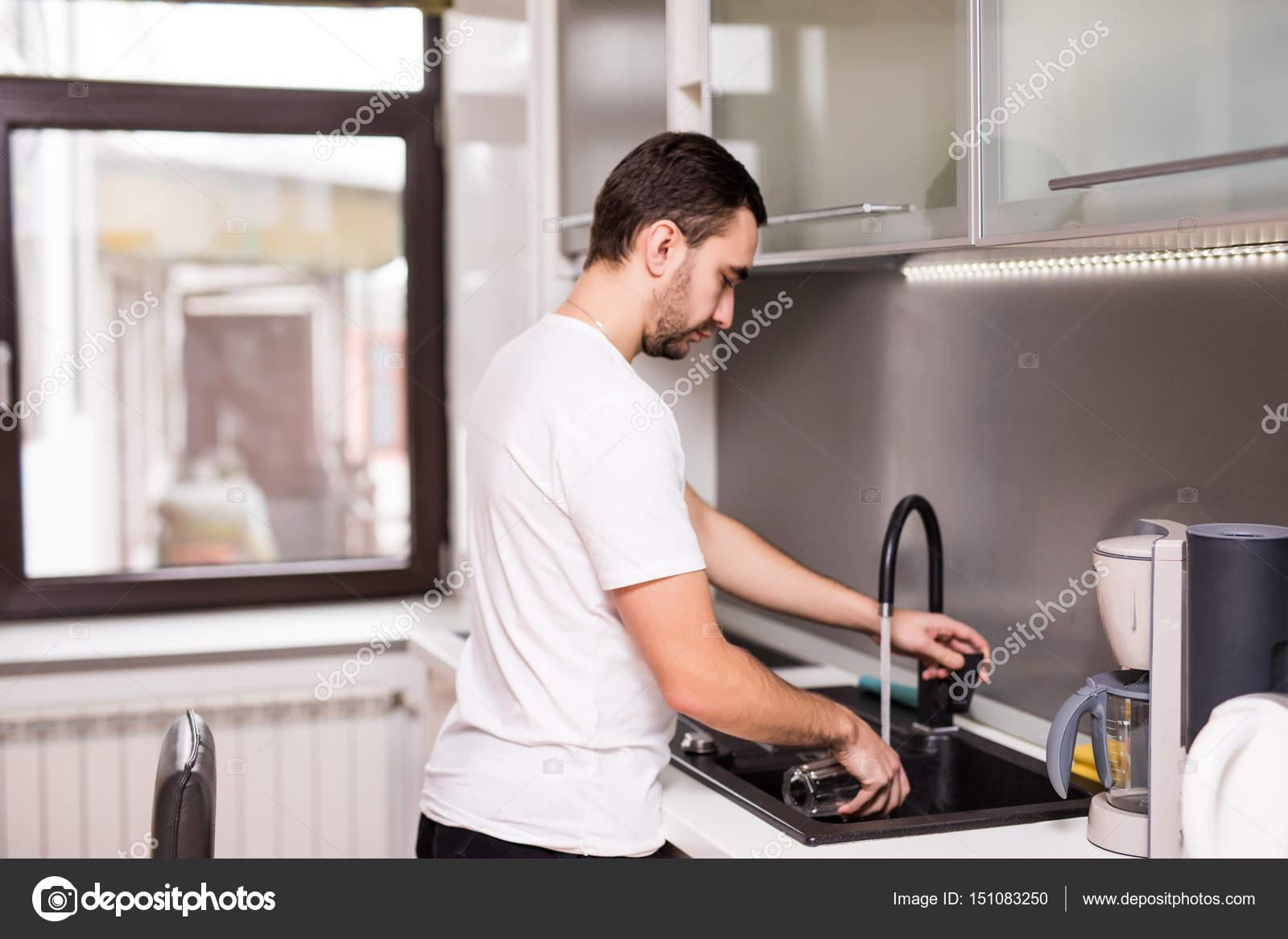Feliz joven hombre de pie y lavar platos en la cocina — Foto de ...