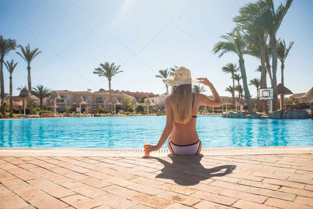 Фотообои back view of young woman in bikini with cocktail summer vocation