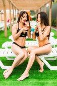 Rückansicht Schöne sexy Frauen im Bikini trinken einen Cocktail, während sie sich im Swimmingpool entspannen. Sommerzeit