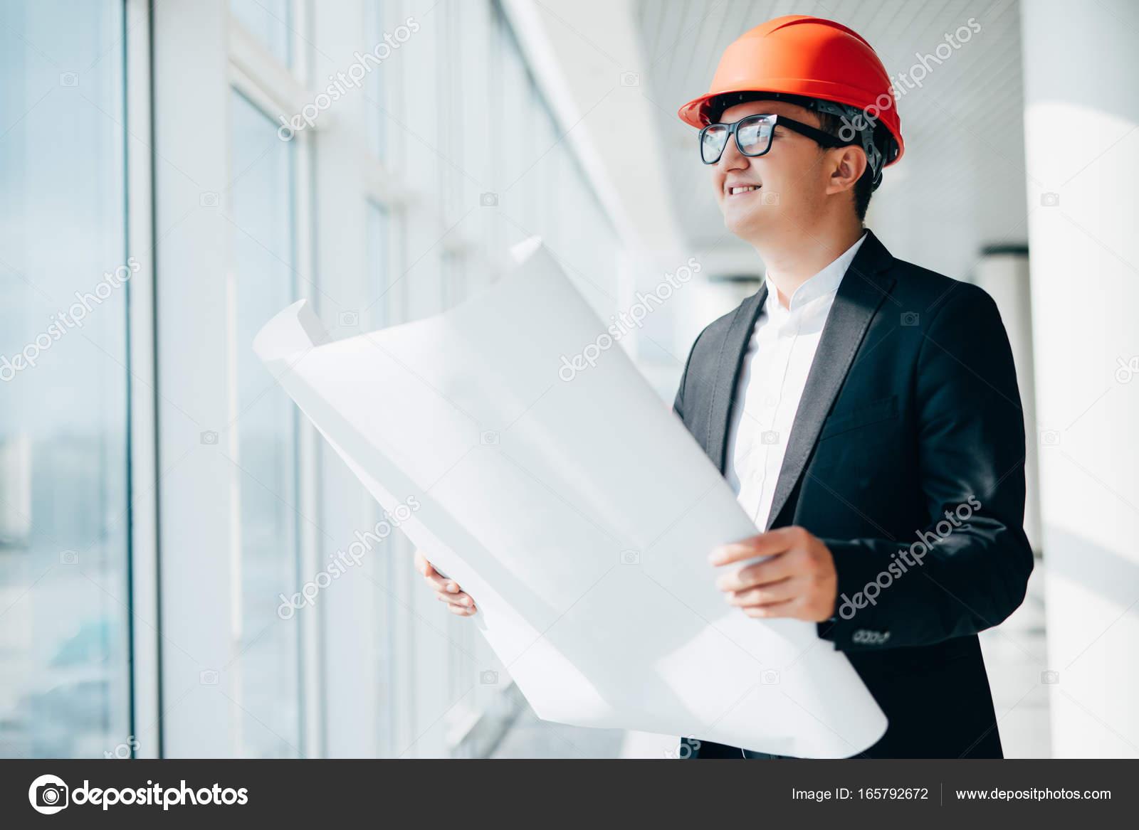 Builder engineer man wear security helmet look at blueprint paper builder engineer wear security helmet look at blueprint paper construction near panoramic windows photo by danytskuail malvernweather Image collections