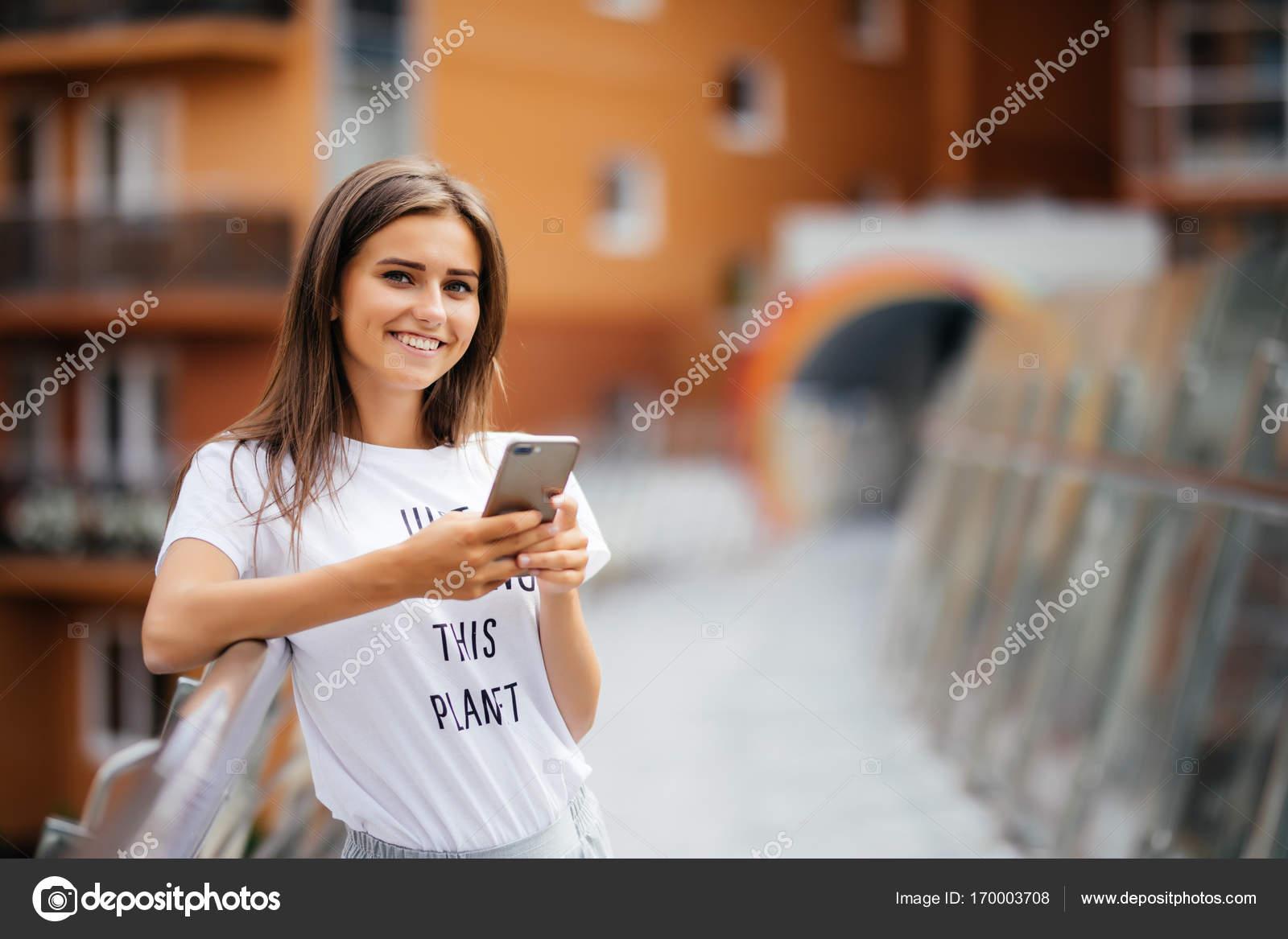 Lifestyle Portrait einer Frau lässig gekleidet stehend mit Telefon ...