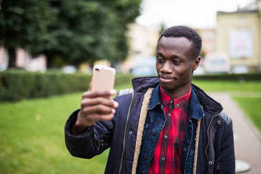 Photo of african happy man holding his cellphone in hands and make a selfie outdoors.